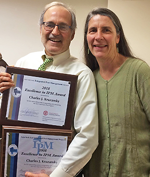 Charlie Kruzansky receives 2 Excellence-in-IPM Awards from IPM Director Jennifer Grant.